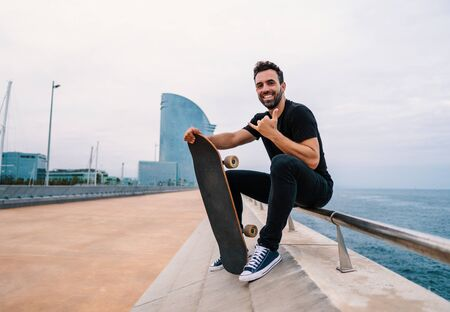 Skateboarder sits with skateboard on the modern city sea terrace