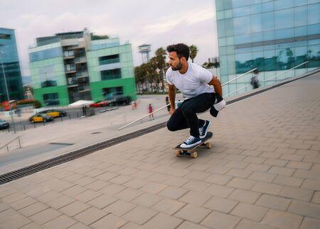 Skateboarder rides a skateboard in the modern city terrace.