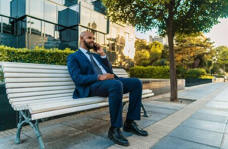 Indian businessman holding mobile phone wearing blue suit