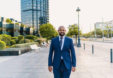 Indian businessman wearing blue suit walking near office or hotel 版權商用圖片