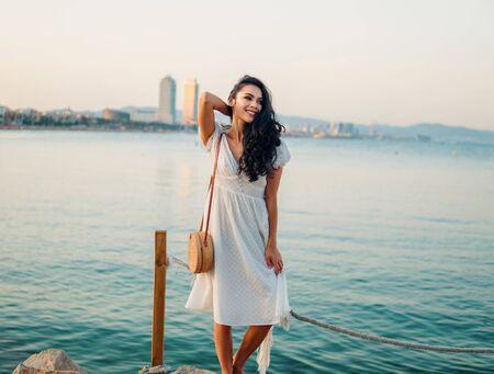 Beautiful girl in the white dress walking along the sea promenade