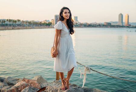 Beautiful girl in the white dress along the sea promenade.