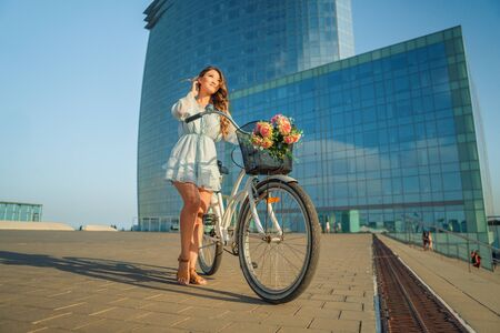 Asian model in a blue dress rides a white bicycle in a green park