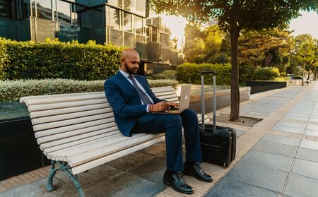 Indian businessman holding laptop notebook wearing blue suit near office