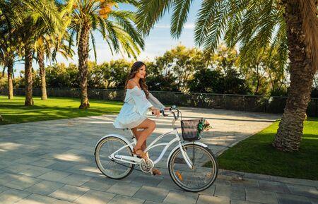 Un mannequin asiatique en robe bleue fait du vélo blanc dans un parc verdoyant