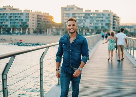 A young handsome man on the bridge near beautiful beach.