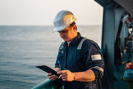 Deck Officer on deck of offshore vessel or ship , wearing PPE personal protective equipment. He fills checklist. Paperwork at sea Archivio Fotografico