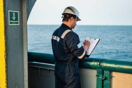 Deck Officer on deck of offshore vessel or ship , wearing PPE personal protective equipment. He fills checklist. Paperwork at sea 版權商用圖片