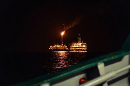Night view of FPSO tanker vessel near Oil Rig.