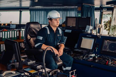 Marine navigational officer during navigational watch on Bridge . Work at sea Фото со стока