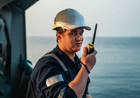 Marine Deck Officer or Chief mate on deck of offshore vessel or ship , wearing PPE personal protective equipment - helmet, coverall. He holds VHF walkie-talkie radio in hands. Archivio Fotografico