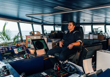 Marine navigational officer during navigational watch on Bridge . Work at sea Stock Photo