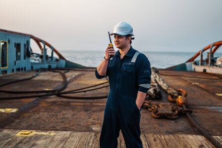 Marine Deck Officer or Chief mate on deck of offshore vessel or ship , wearing PPE personal protective equipment - helmet, coverall. He holds VHF walkie-talkie radio in hands. Stock Photo