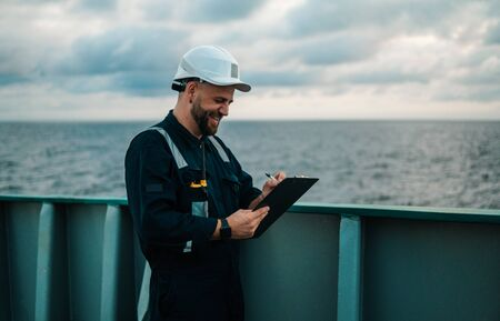 Deck Officer on deck of offshore vessel or ship , wearing PPE personal protective equipment