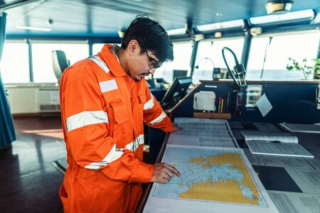 Filipino deck Officer on bridge of vessel or ship. He is plotting position on chart