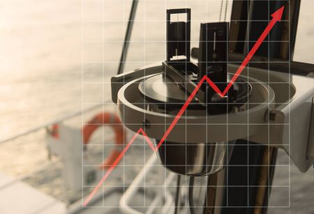 Concept of growth up of marine industry with rising graphics. nautical marine magnetic compass on yacht or boat with orange safety lifebuoy on background.