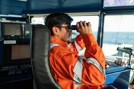 Filipino deck Officer on bridge of vessel or ship looking through binoculars