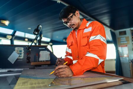 Filipino deck Officer on bridge of vessel or ship. He is plotting position on chart Reklamní fotografie