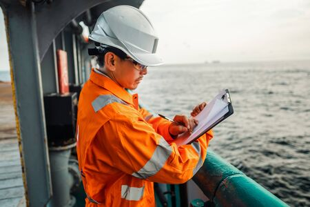 Filipino deck Officer on deck of offshore vessel or ship , wearing PPE personal protective equipment. He fills checklist. Paperwork at sea