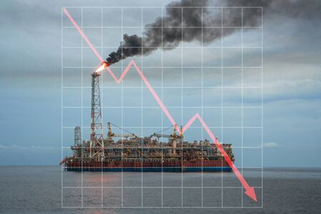 Concept of falling market in oil marine industry with with downward graphics. FPSO tanker vessel on offshore oilfield