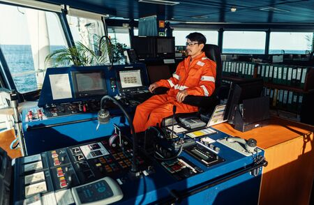 Filipino deck Officer on bridge of vessel or ship. He is looking forward to sea