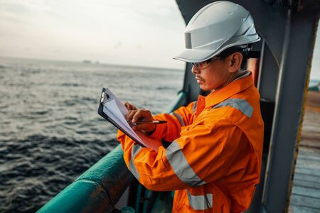 Filipino deck Officer on deck of offshore vessel or ship fills checklist. Paperwork at sea