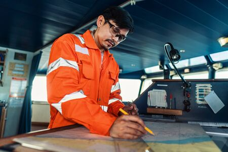 Filipino deck Officer on bridge of vessel or ship. He is plotting position on chart 免版税图像