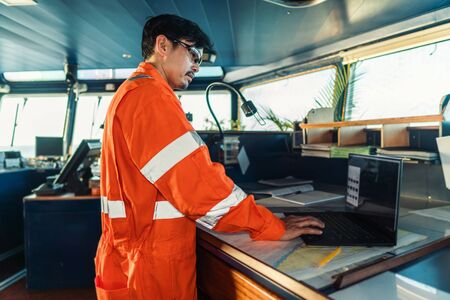 Filipino deck Officer on bridge of vessel or ship. He is using laptop, electronic paperwork at sea