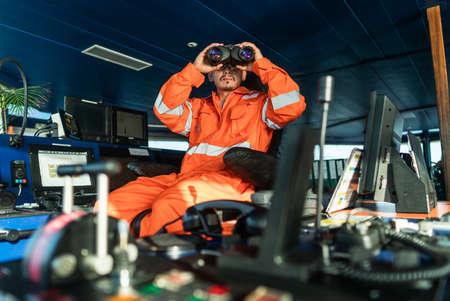 Filipino deck Officer on bridge of vessel or ship looking through binoculars