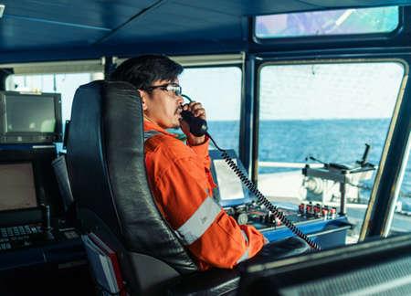 Filipino deck Officer on bridge of vessel or ship. He is speaking on GMDSS VHF radio