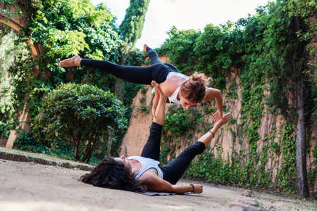 Two beautiful women doing acroyoga in the garden or park