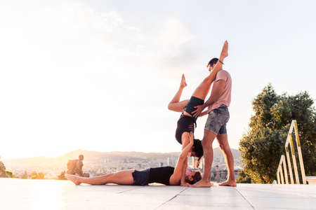 Beautiful man and two women doing acroyoga in the city