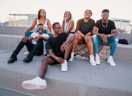 Group of young modern african black friends happily sitting together
