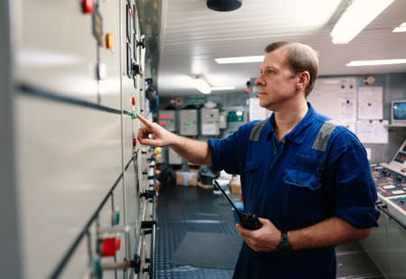 Marine engineer officer controlling vessel engines and propulsion in engine control room Stock Photo