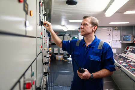 Marine engineer officer controlling vessel engines and propulsion in engine control room 免版税图像