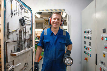 Marine engineer officer controlling vessel enginesand propulsion in engine control room ECR