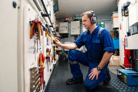 Marine engineer officer in engine control room ECR. He works in workshop