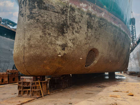Industry view - Ocean Vessel in the dry dock in shipyard. Old rusty ship under repair 免版税图像