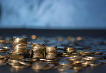 銀行とお金の取引。ダークブルーのぼやけた背景に異なる組み合わせで積み重ねられた金の金属コイン。セルビアの金属コイン、コピースペース