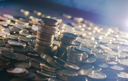 Banking and money trading. Metal coins stacked in different combinations on dark blue blurred background and lens flare. Serbian metal coins, copy space. Close up of metal money. Business concept Reklamní fotografie
