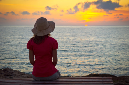 Young woman in hat sitting and looking at sunset photo