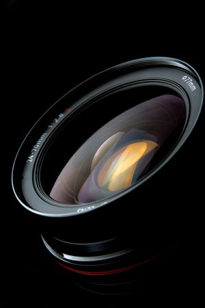 back to camera: Photo lens with reflections on black background