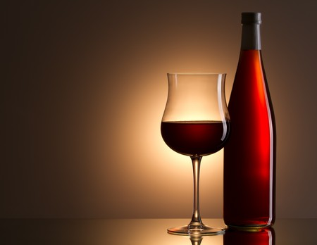 Still-life with the rose wine glass and bottle on gold Stock Photo