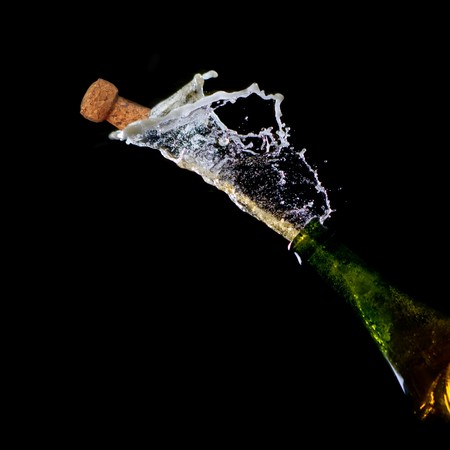 popping the cork: Bottle of Champagne with popping cork and Champagne spray on black background.