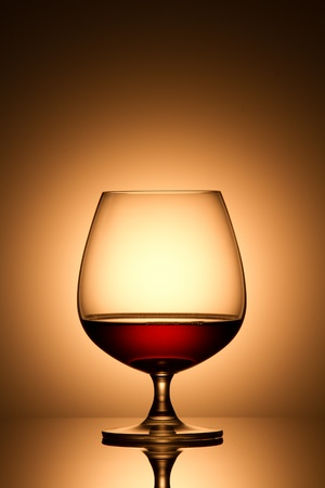 Glass of brandy over gold background photo
