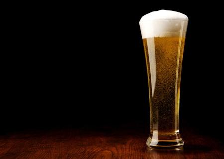 botellas de cerveza: Cerveza en un vaso sobre una mesa de madera y negro