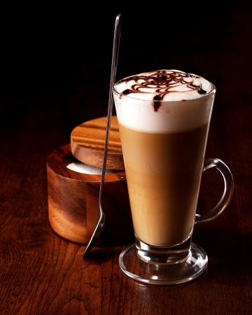 frappe: latte mug on a wooden table with a spoon and sugar