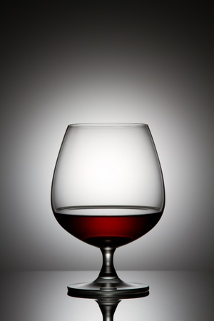 Glass of brandy over gray background photo