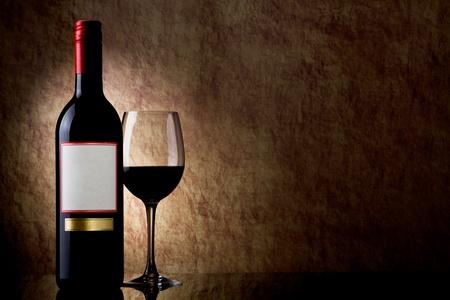 Flasche mit Rotwein und Glas auf einem alten Stein Lizenzfreie Bilder