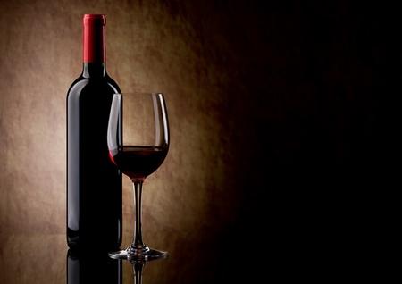 botella de licor: botella con vino tinto y vidrio Foto de archivo